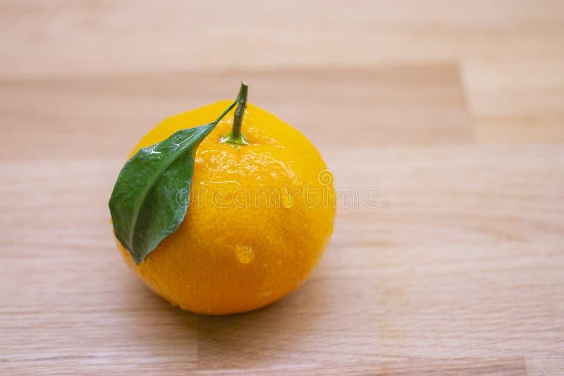 Frische reife Mandarine mit grünen Blatt- und Wassertropfen Nass orange appetitanregende Zitrusfruchtmandarine auf einem Holztisc lizenzfreie stockbilder