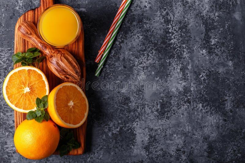 Frische reife Orangen und Saft auf Steintabelle lizenzfreie stockbilder
