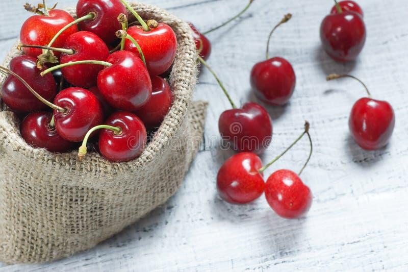 Frische reife organische rote Kirschen im Leinwandsack auf hölzernem Hintergrund stockfotos
