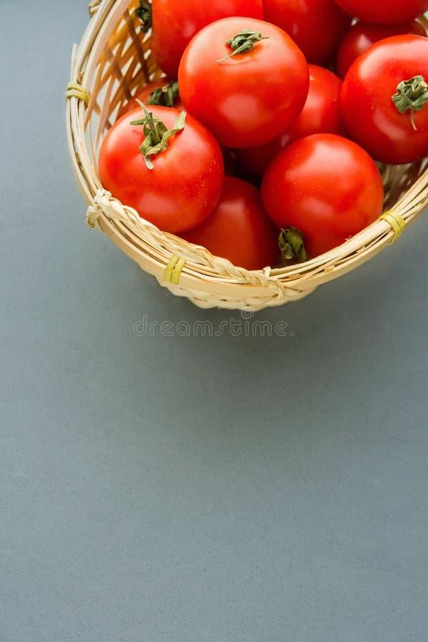 Frische reife organische rote Tomaten im Weidenkorb auf Grey Background Frische und saftige Schinken- und Melonesonne formte Hint lizenzfreie stockfotografie