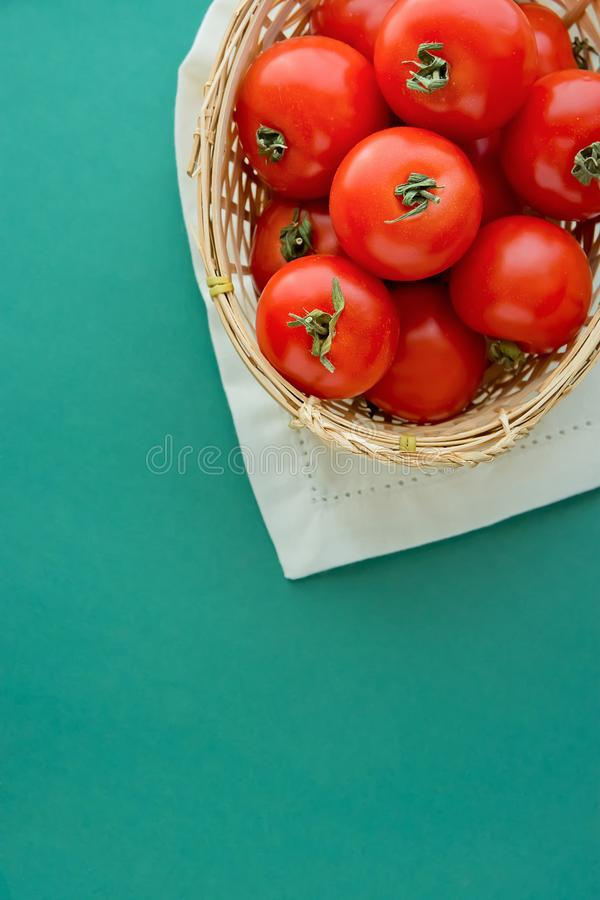 Frische reife organische rote Tomaten im Weidenkorb auf weißem Servietten-Grün-Hintergrund Nachahmung von italienischen Staatsfla lizenzfreies stockfoto