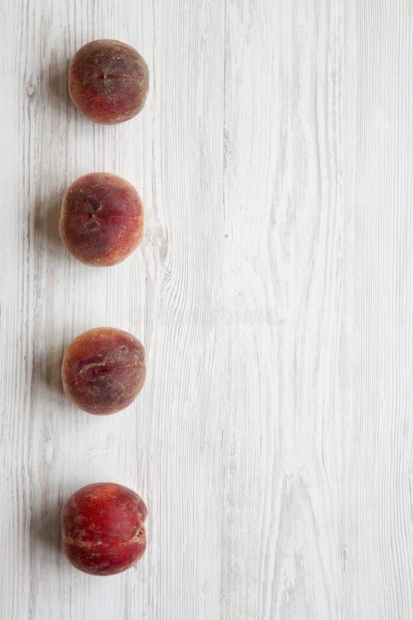 Frische reife Pfirsiche auf weißem hölzernem Hintergrund, Draufsicht stockfotos