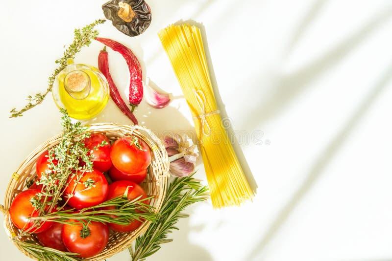 Frische reife rote Tomaten Rosemary Thyme im Weidenkorb Olive Oil in den Flaschen-Spaghetti-Peperoni auf weißer Tabelle Italienis lizenzfreie stockfotos