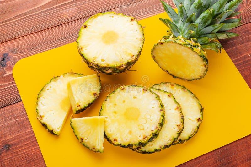 Frische reife tropische Ananas geschnitten in Scheiben auf einem gelben rackside, das auf einem Holztisch liegt lizenzfreies stockbild
