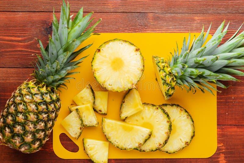 Frische reife tropische Ananas geschnitten in Scheiben auf einem gelben rackside, das auf einem Holztisch liegt lizenzfreies stockfoto
