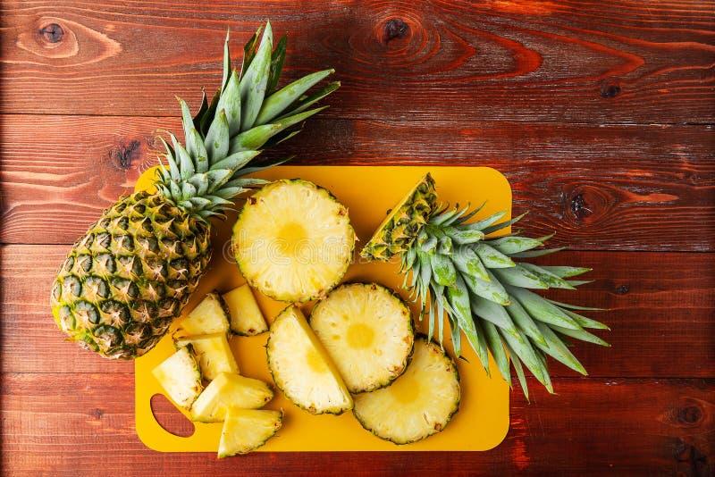Frische reife tropische Ananas geschnitten in Scheiben auf einem gelben rackside, das auf einem Holztisch liegt stockfotos