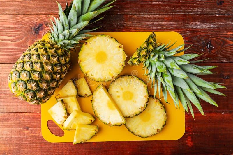 Frische reife tropische Ananas geschnitten in Scheiben auf einem gelben rackside, das auf einem Holztisch liegt stockfoto
