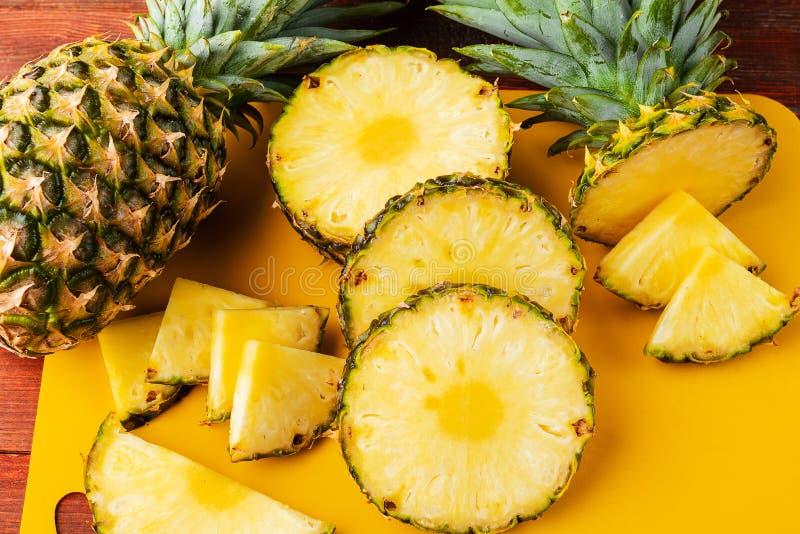 Frische reife tropische Ananas geschnitten in Scheiben auf einem gelben rackside, das auf einem Holztisch liegt stockbilder