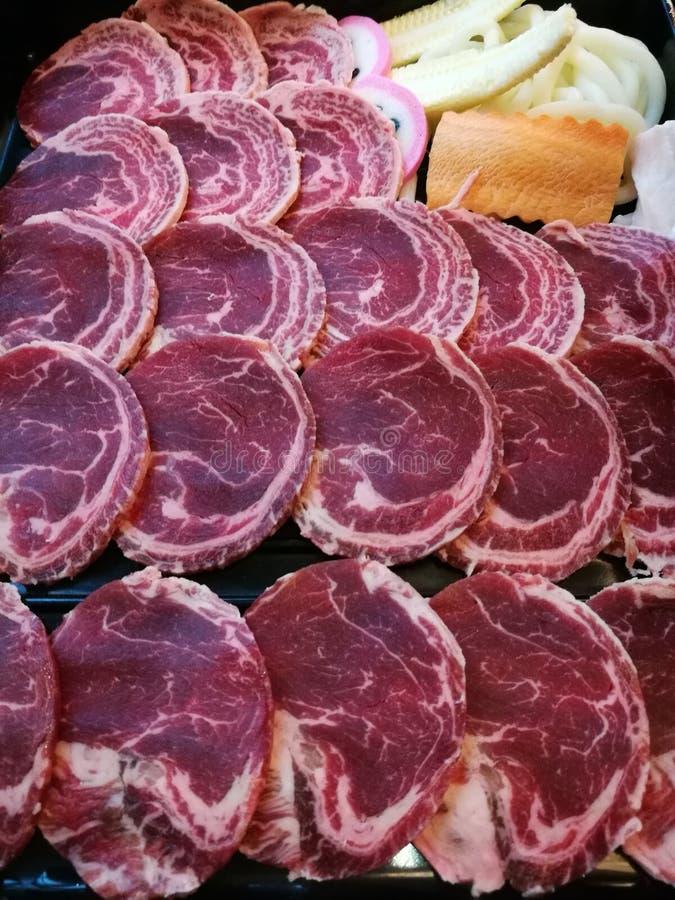 Frische Rindfleischscheibenumhüllung auf dem Behälter mit etwas Gemüse, Karottenmais und Kohl stockbilder