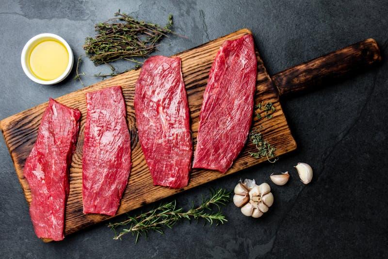 Frische Rindfleischsteaks des rohen Fleisches Rindsfilet auf hölzernem Brett, Gewürze, Kräuter, Öl auf Schiefergrauhintergrund Le lizenzfreie stockfotos