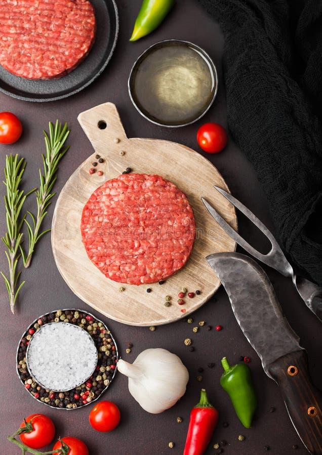 Frische rohe gehackte selbst gemachte Landwirte grillen Rindfleischburger auf rundem hackendem Brett mit Gew?rzen und Kr?uter und stockfotografie
