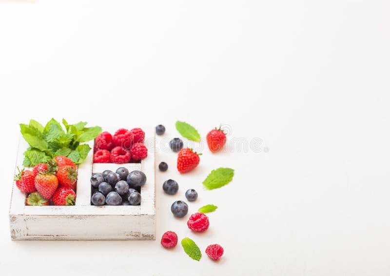 Frische rohe organische Beeren in der weißen Holzkiste auf weißem Küchentischhintergrund Raum für Text Beschneidungspfad eingesch lizenzfreie stockfotos