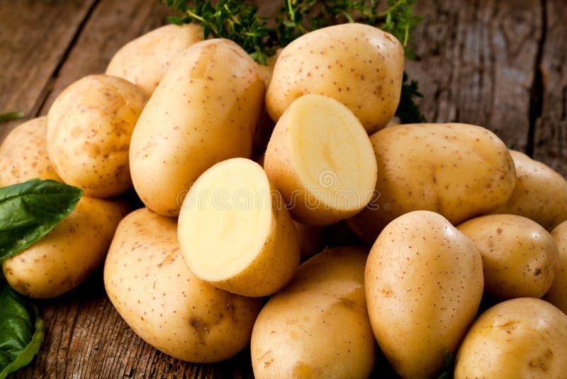 Frische rohe organische Kartoffeln auf altem Weinlesehintergrund stockbilder