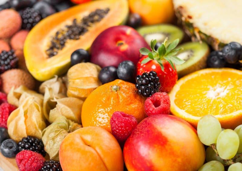 Frische rohe organische Sommerbeeren und exotische Früchte Makro Abschluss oben Ananas, Papaya, Trauben, Nektarine, Orange, Aprik stockfotografie
