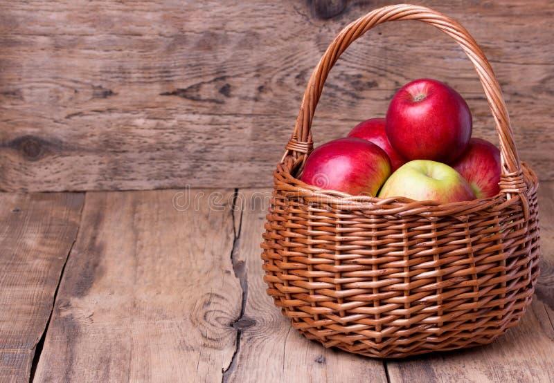 Frische rote Äpfel im Korb über hölzernem Hintergrund lizenzfreies stockfoto