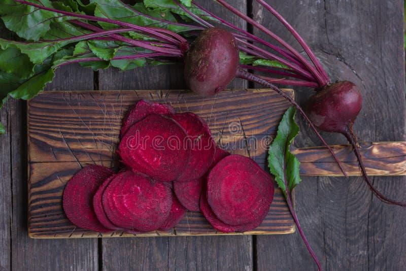 Frische Rote-Bete-Wurzeln mit Blättern auf hölzerner Tabelle Ganzes und geschnittene Rote-Bete-Wurzeln lizenzfreie stockfotografie