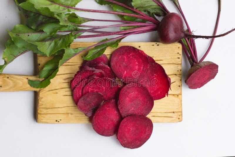 Frische Rote-Bete-Wurzeln mit Blättern auf hölzerner Tabelle Ganzes und geschnittene Rote-Bete-Wurzeln lizenzfreie stockbilder