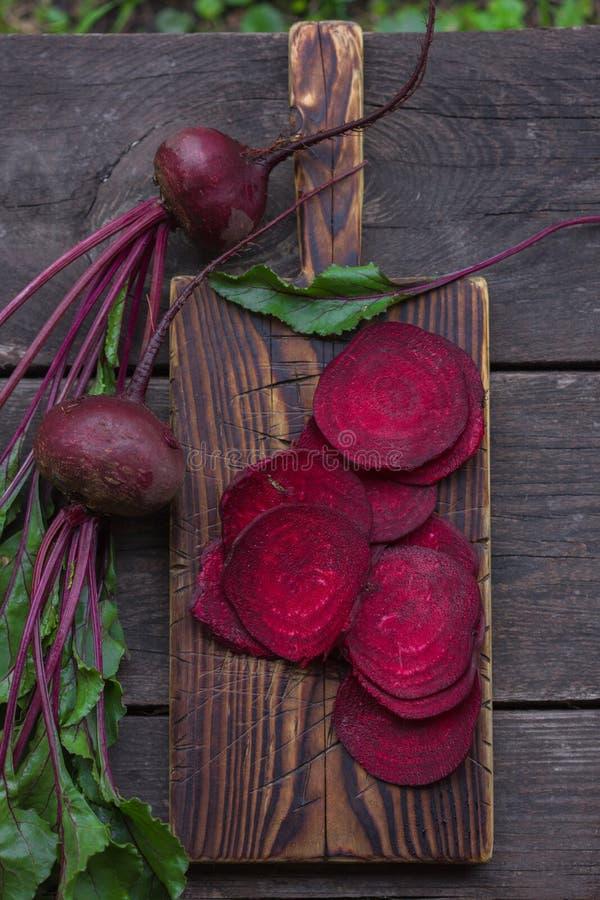 Frische Rote-Bete-Wurzeln mit Blättern auf hölzerner Tabelle Ganzes und geschnittene Rote-Bete-Wurzeln stockbilder