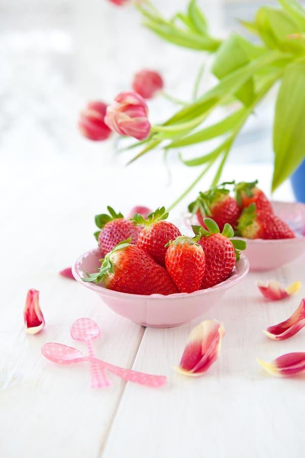 Frische rote Erdbeeren und Tulpen lizenzfreies stockfoto