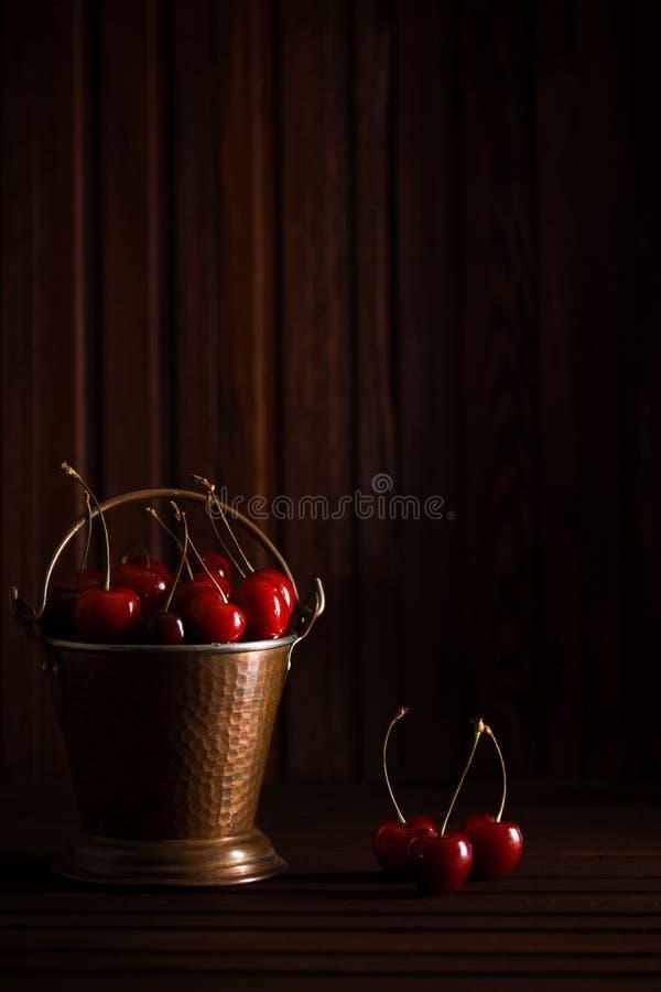Frische rote Kirschen im kupfernen Eimer auf dunklem hölzernem Hintergrund stockfotografie