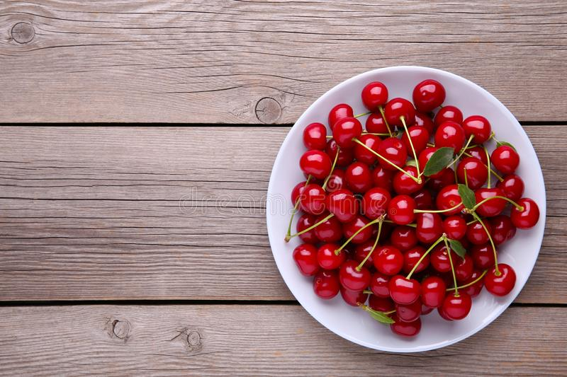 Frische rote Kirschfrucht in der Platte auf grauem Holztisch stockfotografie