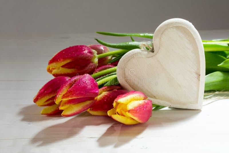 Frische rote orange Tulpen und ein hölzernes Herz, Liebesdekoration für stockbild