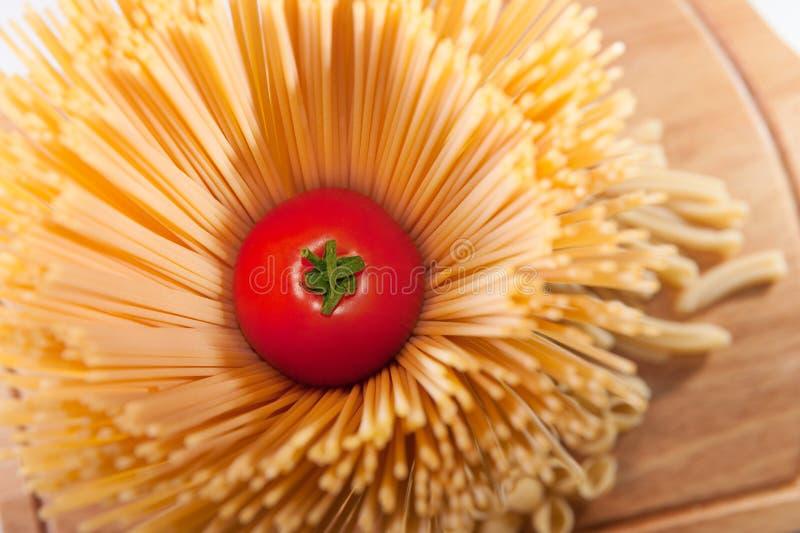 Frische rote Tomate innerhalb der Isolationsschlauchteigwaren lizenzfreie stockfotografie