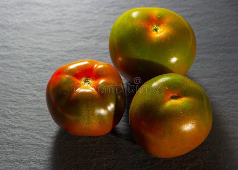 Frische rote Tomaten auf dunkler Steintabelle oder schwarzem Hintergrund lizenzfreie stockfotografie