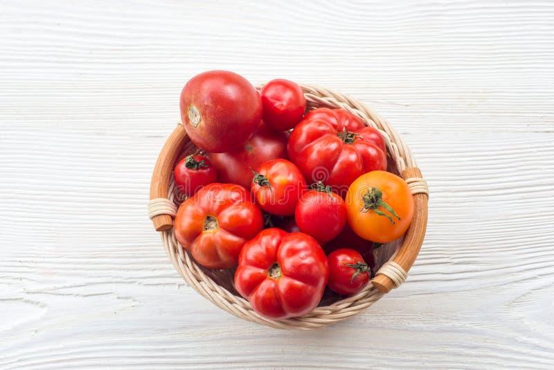 Frische rote Tomaten in einem Korb auf einem weißen Hintergrund stockfotografie