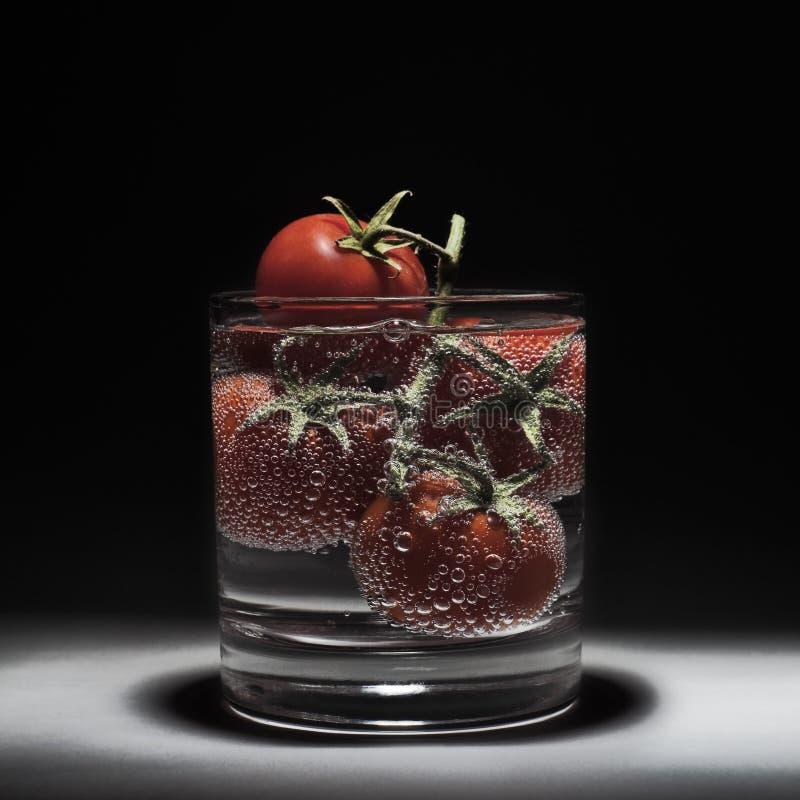 Frische rote Tomaten im Wasser lokalisiert auf einem schwarzen Hintergrund Luftblasen des Wassers Niederlassung von Tomaten lizenzfreie stockbilder
