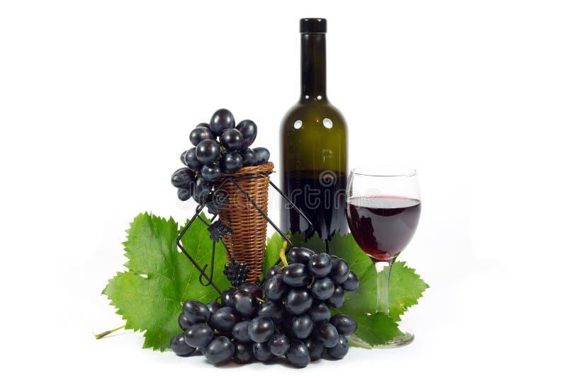 Frische rote Trauben mit den grünen Blättern, Wein-Glas-Schale und der Wein-Flasche gefüllt mit dem Rotwein lokalisiert auf Weiß lizenzfreie stockbilder