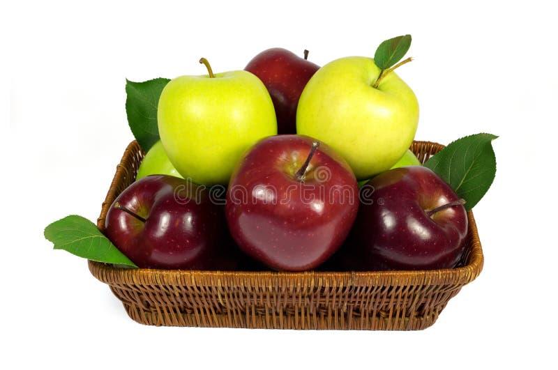 Frische rote und grüne Äpfel mit Blättern im Weidenkorb lokalisiert auf Weiß lizenzfreie stockfotografie