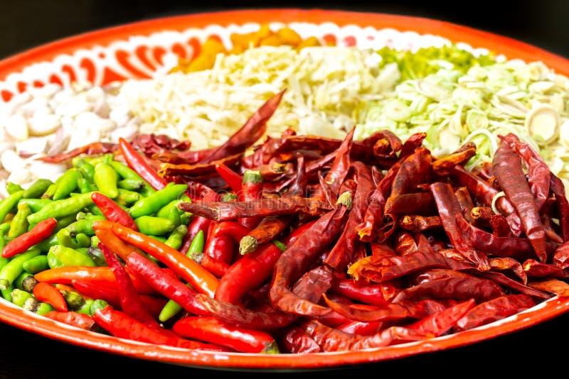Frische rote und grüne und getrocknete Paprikabeiträge zu thailändischem rotem Curry-Pasten-Rezept stockbild