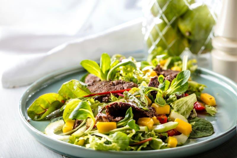 Frische Salatplatte mit Mischgrüns Arugula, mesclun, mache auf dunklem hölzernem Hintergrundabschluß oben MANZO lizenzfreies stockfoto