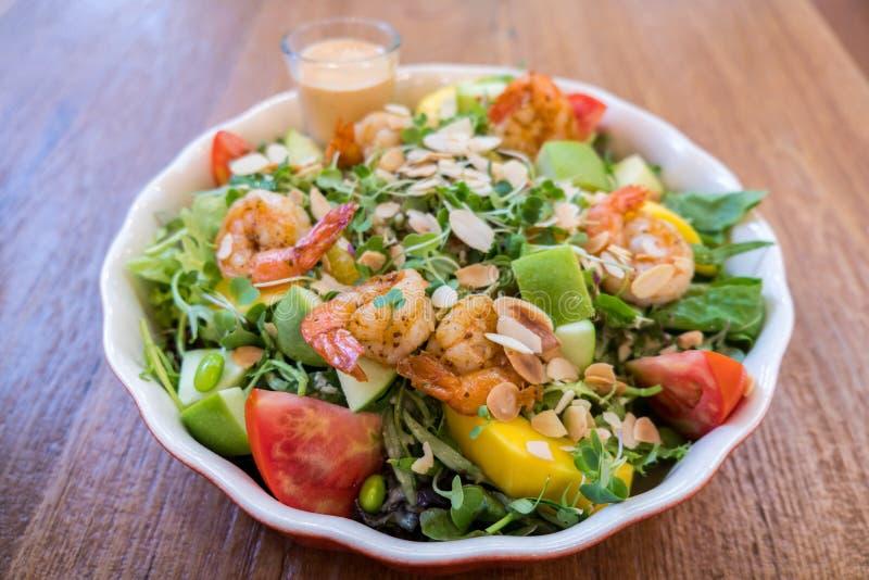Frische Salatschüssel mit Garnele, Tomate, Apfel und Mischgrünsalat auf Holztischhintergrund lizenzfreies stockfoto