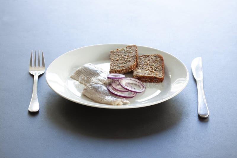 Frische Salzheringe auf einer Platte mit homebaked rustikalem gesätem Roggenbrot und Zwiebelringen mit Tischbesteck Skandinavisch lizenzfreie stockfotos