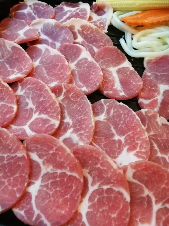 Frische Schweinefleischscheibenumhüllung auf dem Behälter mit etwas Gemüse, Karottenmais und Kohl stockbilder