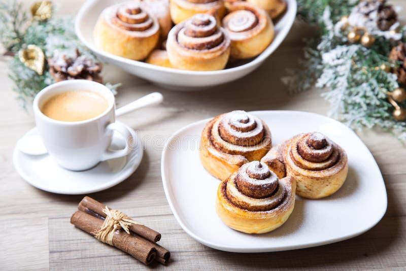 Frische selbst gemachte Brötchen mit Zimt, ein Tasse Kaffee, Zimtstangen stockfotos