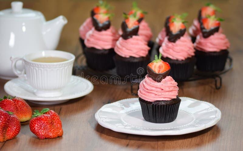 Frische selbst gemachte Schokoladenkleine kuchen mit buttercream und Erdbeeren lizenzfreie stockbilder