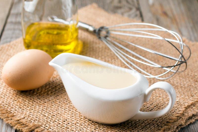 Frische selbst gemachte weiße Soße Majonäse und Bestandteileier, Olivenöl der Zitrone auf hölzernem Hintergrund stockbild