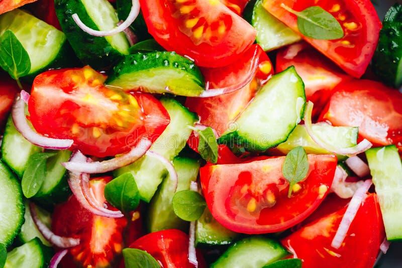 Frische Sommersalatschüssel mit Tomaten, Gurken, rote Zwiebeln, Basilikumnahaufnahme stockfoto