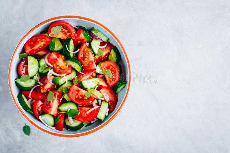 Frische Sommersalatsch?ssel mit Behandlung der Tomaten, der Gurken, der roten Zwiebeln, des Basilikums und des Oliven?ls stockfotografie