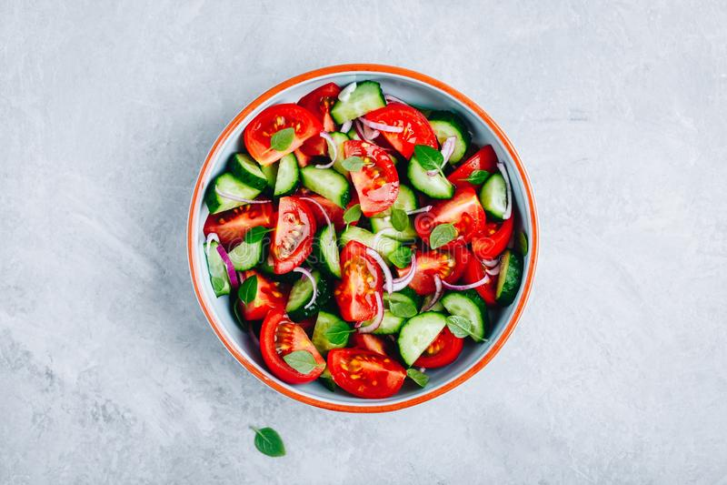 Frische Sommersalatsch?ssel mit Behandlung der Tomaten, der Gurken, der roten Zwiebeln, des Basilikums und des Oliven?ls stockbilder