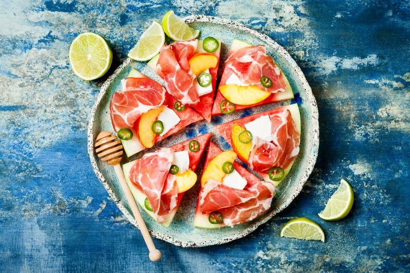 Frische Sommerwassermelonenpizza mit Feta, Pfirsich, Prosciutto, Jalapeno und Honig nieselt auf blauem Hintergrund lizenzfreies stockbild