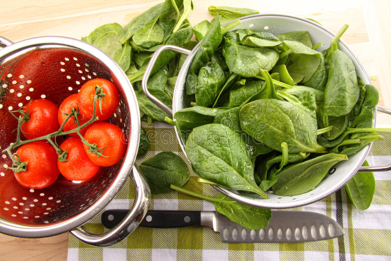 Frische Spinatblätter mit Tomaten lizenzfreies stockfoto