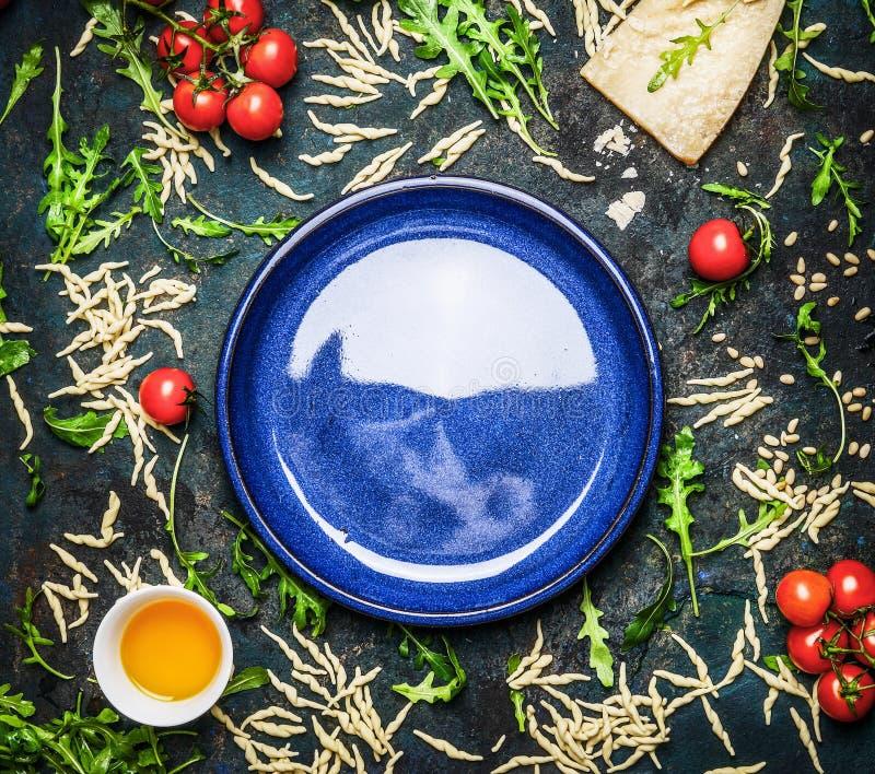 Frische Teigwaren mit Bestandteilen für das geschmackvolle Kochen um leere Platte auf rustikalem Weinlesehintergrund, Draufsicht stockfoto
