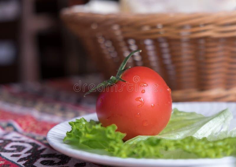 Frische Tomate auf der Platte mit grünem Blatt stockfotos