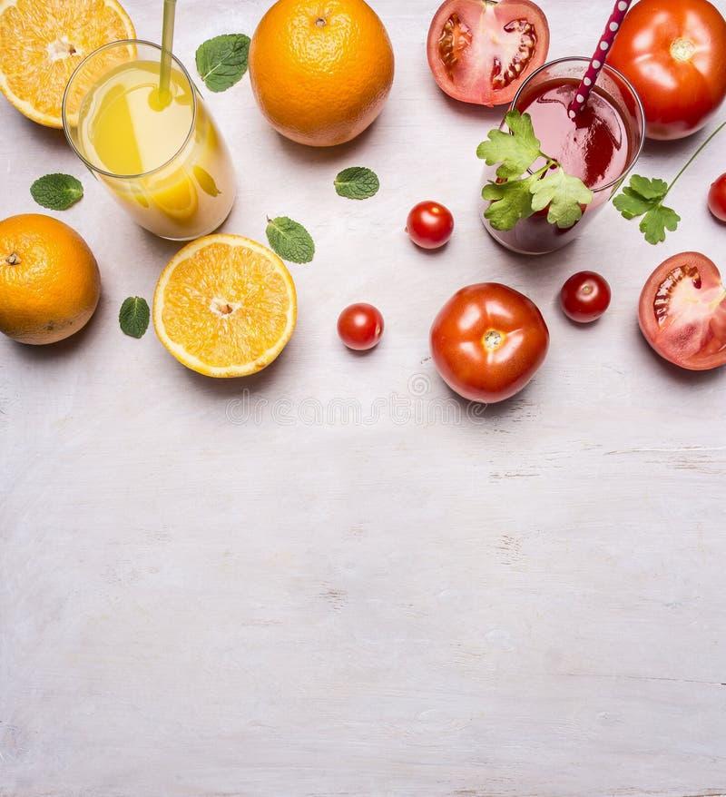 Frische Tomate und Orangensäfte mit Minze in den Gläsern mit Strohgrenze, Platz für Draufsichtabschluß des Hintergrundes des Text lizenzfreie stockfotos