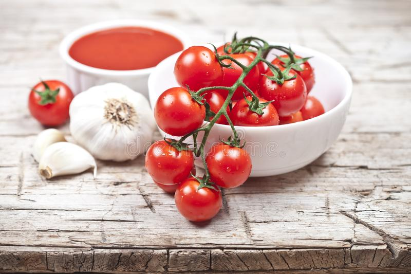 Frische Tomaten in der weißen Schüssel, in der Soße und im rohen Knoblauch auf rustikalem Holztisch stockfotografie