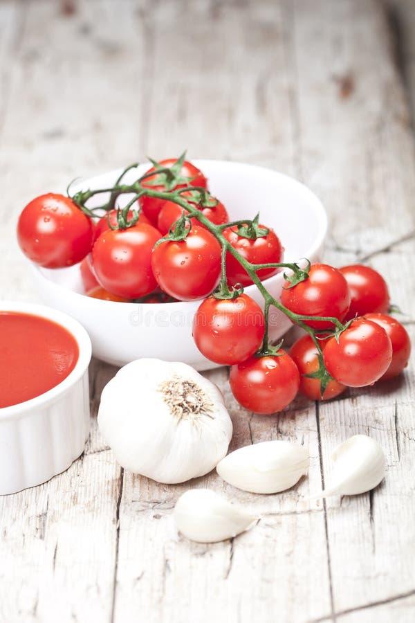 Frische Tomaten in der weißen Schüssel, in der Soße und im rohen Knoblauch auf rustikalem Holztisch stockbilder